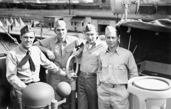Left to right: Marty E Roberts, Lieutenant (jg) (Ensign, Engineering Officer) of Rockville Centre, Long Island, NY; Al B Wiles, Lieutenant (jg) (Skipper, Commanding Officer) from Jackson, MS; Clint J Hill, Ensign (4th Officer, Communications Officer) of Seattle, WA; and Dave V Stafford, Lieutenant (jg) (Executive Officer) of CA; at port in Little Creek, VA; September 1944